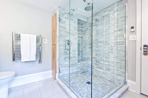 Contemporary interior bathroom design with glass enclosed shower stall with Cararra marble tiles. Duo shower heads with rain shower and conventional shower head. Heated towel rack hanger. Photographed in horizontal format.